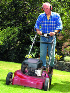 Photo, senior man mowing the grass wearing hearing protection, Color, High res